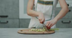 La donna nel suo gabinetto della cucina ha tagliato un grande sedano con un grande coltello sul selettore rotante, tagli professi stock footage