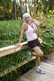 La donna nell'allenamento copre l'acqua potabile di sosta Fotografia Stock