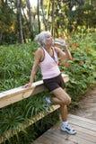 La donna nell'allenamento copre l'acqua potabile di sosta Fotografia Stock Libera da Diritti