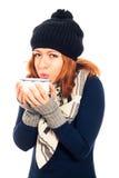 La donna nell'inverno copre la tazza della tenuta con la bevanda calda Immagine Stock