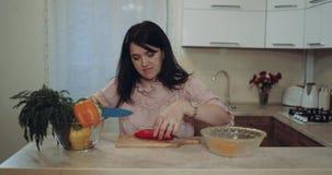 La donna nella cucina prepara le verdure renderla all'alimento felice le ha tagliate 4K video d archivio