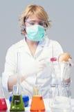 La donna nella maschera protettiva verifica l'esemplare della mela in laboratorio chimico Immagini Stock