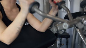 La donna nella palestra sul simulatore stringe il suo bicipite sulle mani archivi video