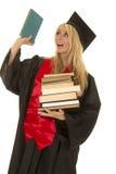 La donna nella pila nera dell'abito di graduazione di libri tiene uno su Fotografia Stock