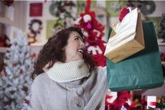 La donna nello sguardo del negozio ha soddisfatto i suoi sacchetti della spesa fotografia stock libera da diritti