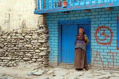 La donna nepalese anziana in un vestito tradizionale sta vicino alla parete blu, sulla via nel villaggio di Kagbeni del regno Mus Fotografie Stock