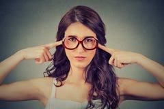 La donna nerd in vetri che tappano le orecchie con le dita non vuole ascoltare Fotografia Stock