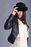 La donna in nero tocca il suo cappello Fotografie Stock Libere da Diritti