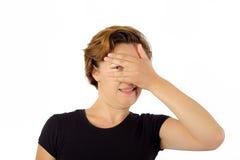 La donna non può distogliere lo sguardo Guardando tramite la mano sul fronte Immagini Stock Libere da Diritti