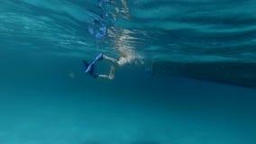 La donna nuota lentamente alla barca nell'oceano stock footage