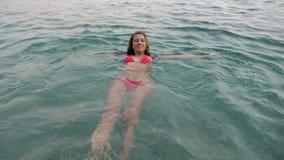La donna nuota nel mare, cade nell'acqua e si diverte, esaminando la macchina fotografica archivi video