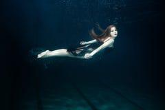 La donna nuota underwater Immagine Stock