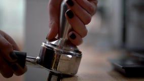 La donna o il barista preme il caffè macinato nel supporto per fare un caffè delizioso ed andare inserire il caffè video d archivio
