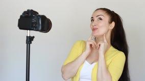 La donna o il blogger sorridente felice gestures con le mani e parla, registrando il video su una macchina fotografica che è ripa archivi video