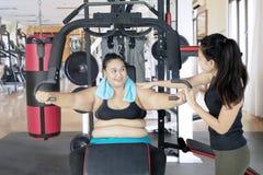 La donna obesa ha assistito dal suo istruttore all'allenamento Immagini Stock