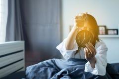 La donna odia ottenere sollecitata svegliando presto 7 in punto di mattina, sveglia fotografia stock
