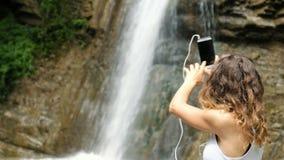 La donna ondeggia il suo telefono, colloqui in cuffie via il video collegamento e mostra una cascata stock footage