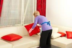 La donna organizza i cuscini sul sofà fotografia stock