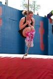 La donna oscilla la corda attraverso l'ostacolo nella corsa pazza 5K Immagine Stock