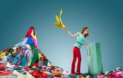 La donna ottiene i vestiti dalla borsa Fotografie Stock Libere da Diritti