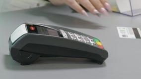 La donna paga con la carta di credito facendo uso del terminale in un negozio video d archivio