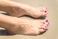 La donna paga con un anello su un dito del piede fotografia stock libera da diritti