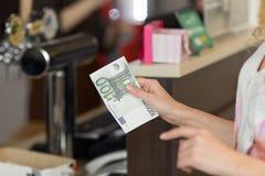 La donna paga in contanti per la prima colazione nel caffè con le euro banconote Fotografia Stock Libera da Diritti