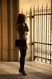 La donna parigina di modo con il telefono e il chanel insaccano in galery della feritoia Fotografie Stock Libere da Diritti