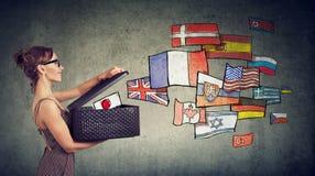 La donna parla le lingue differenti che aprono una scatola con le bandiere internazionali che volano via fotografia stock