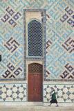 La donna passa dalla parete del mausoleo di Khoja Ahmed Yassawi in Turkistan, il Kazakistan Immagine Stock