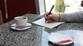 La donna passa il caffè e la scrittura della tenuta nell'ordine del giorno quotidiano del pianificatore di affari stock footage