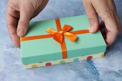 La donna passa il colore del turchese del contenitore di regalo di apertura Fotografia Stock