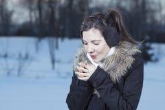 La donna passa l'alito caldo fotografia stock