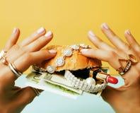 La donna passa l'hamburger della tenuta con soldi, gioielli, cosmetico, fine sociale di concetto di ricchezza dell'edizione su fotografia stock