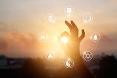 La donna passa l'icona di religioni e pregare sul fondo del tramonto immagini stock
