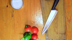 La donna passa la cottura delle verdure sul tagliere che rustico la cima giù osserva stock footage