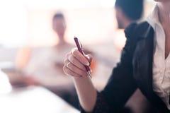 La donna passa la penna di tenuta sulla riunione d'affari Immagine Stock