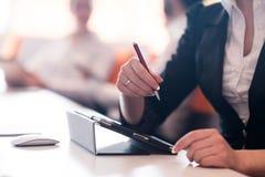 La donna passa la penna di tenuta sulla riunione d'affari Fotografie Stock Libere da Diritti