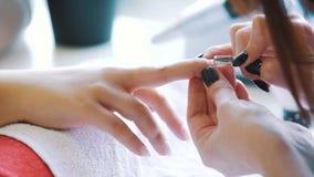 La donna passa la ricezione del manicure nel salone di bellezza Limatura del chiodo Chiuda su, fuoco selettivo stock footage