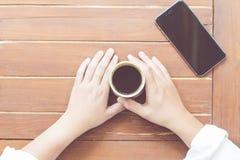 La donna passa la tenuta della tazza di caffè caldo Fotografia Stock