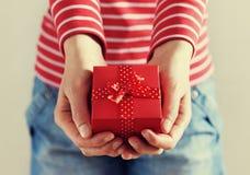 La donna passa la tenuta un regalo o della scatola attuale con l'arco del nastro rosso Fotografia Stock Libera da Diritti