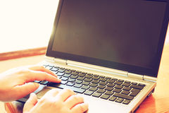 La donna passa lavorare al computer portatile vicino alla finestra con luce naturale Fotografia Stock