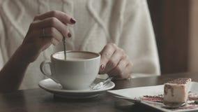 La donna passa lo zucchero di versamento alla tazza in caffè stock footage