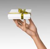 La donna passa a presente di festa della tenuta la scatola bianca con il nastro dorato giallo Fotografia Stock Libera da Diritti