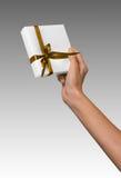 La donna passa a presente di festa della tenuta la scatola bianca con il nastro dorato giallo Immagine Stock