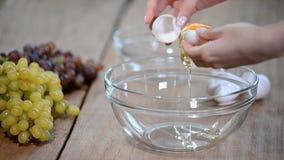 La donna passa la rottura dell'uovo per separare la chiara dell'uovo e tuorli e coperture dell'uovo ai precedenti archivi video