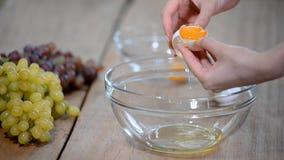 La donna passa la rottura dell'uovo per separare la chiara dell'uovo e tuorli e coperture dell'uovo ai precedenti stock footage