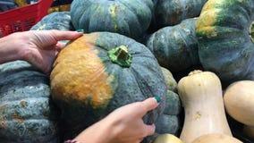 La donna passa la scelta della zucca organica fresca nel supermercato l'asia video d archivio