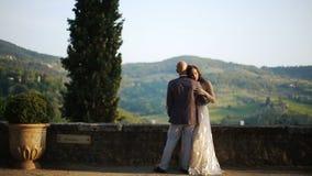 La donna pende l'offerta al suo uomo che sta sul balcone con grande paesaggio dietro archivi video