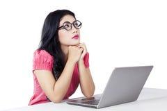 La donna pensierosa con il computer portatile immagina qualcosa Immagine Stock